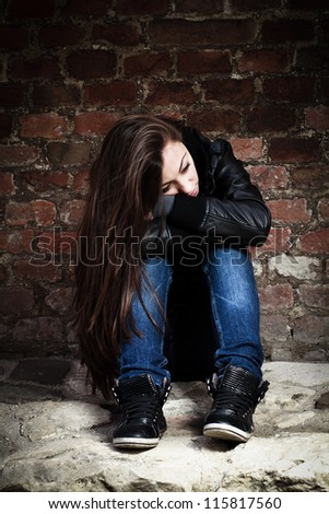 Sad teenage girl, leaning on an old brick wall.