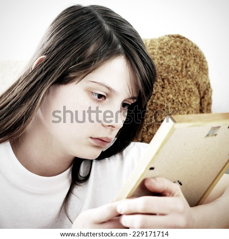 Sad Teenage Girl looking on the Photo Frame - stock photo
