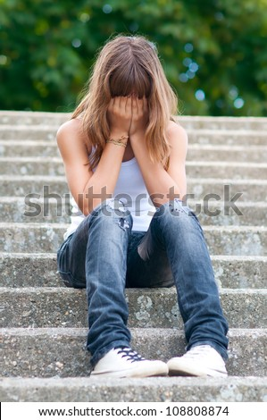 Sad teenage girl sitting alone on the stairs. - stock photo