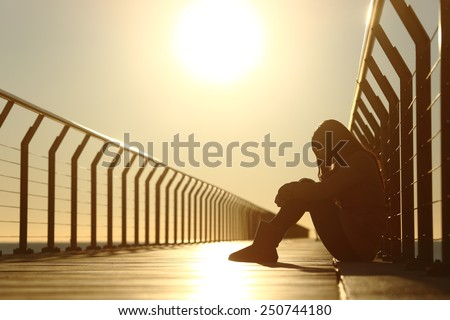 Sad teenager girl depressed sitting in the floor of a bridge on the beach at sunset - stock photo