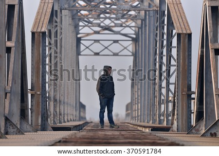 Sad teenager in depression sitting on the bridge at the sunset. Concept teenage problems. Selective focus - stock photo
