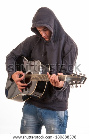 Sad teenager in hoodie playing acoustic guitar. Trying to write a song about teenage problems - stock photo