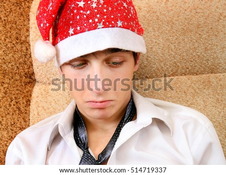 Sad Teenager in Santa Hat on the Sofa at the Home