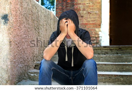 Sad Teenager in the Hood on the Old House Background