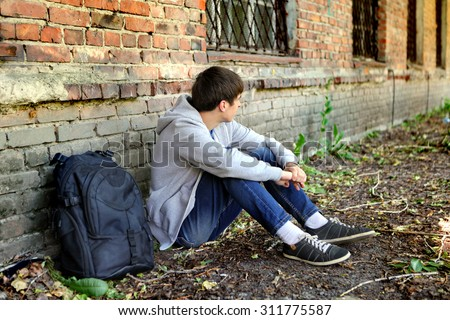 Sad Teenager near the Brick Wall of the Old House
