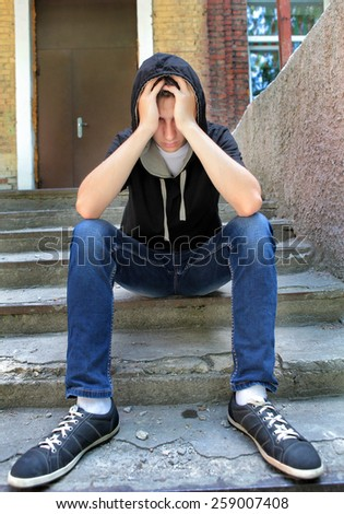 Sad Teenager on the landing steps of the Old House - stock photo