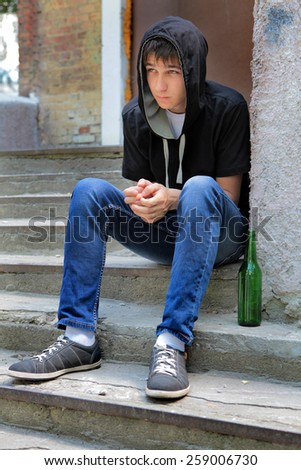Sad Teenager on the landing steps with a Bottle of the Beer - stock photo