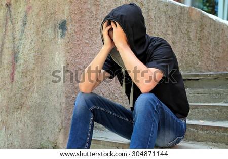 Sad Teenager sit on the City Street - stock photo