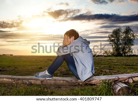 Sad Teenager sit on the Log on the Sunset Background