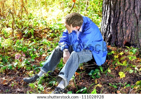 sad teenager sitting in the autumn forest