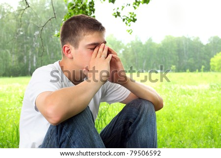 sad teenager sitting in the forest alone - stock photo