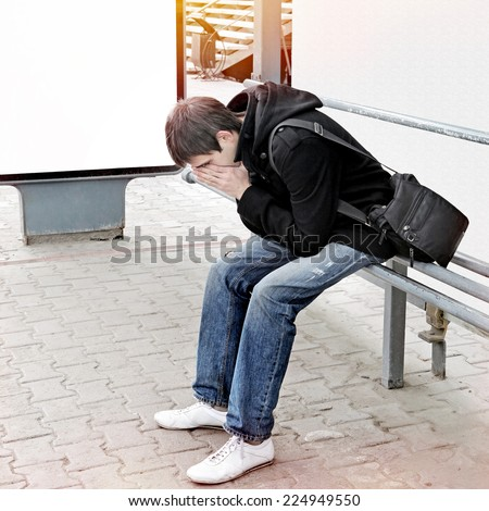 Sad Teenager Sitting on the Bench at the City Street - stock photo