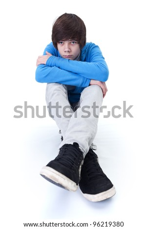 Sad teenager thinking and daydreaming while sitting on the floor - isolated - stock photo