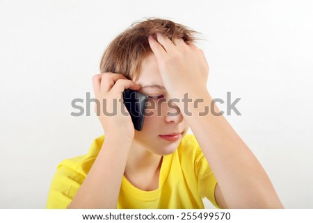 Sad Teenager with Cellphone on the White Background - stock photo