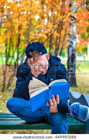 Sad Teenager with the Book in the Autumn Park - stock photo