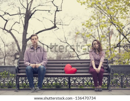 Sad teens sitting at the bench at the park - stock photo