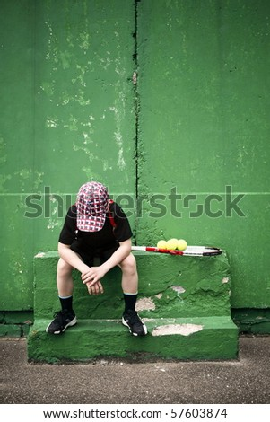 Sad tennis player having rest in front of old training wall - stock photo
