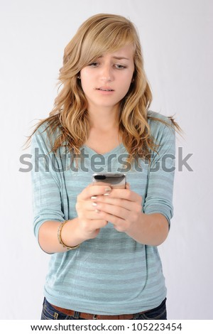 Sad Text Message Received. Teenage girl reacting to a sad text message received on her smartphone. Note: Not Isolated. - stock photo