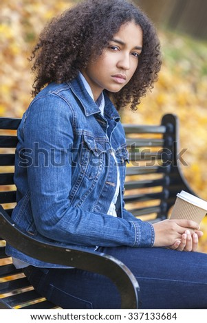 Sad thoughtful or depressed mixed race African American girl teenager female young woman drinking takeaway coffee outside sitting on a park bench in autumn or fall - stock photo