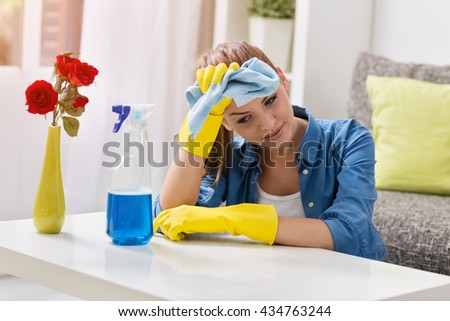 Sad tired frustrated and exhausted woman cleaning home - stock photo