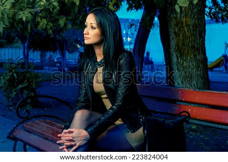 Sad unhappy woman sitting on bench in loneliness and looking away - stock photo