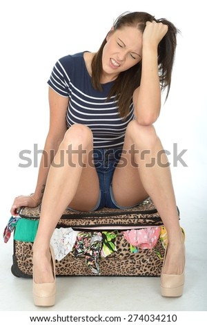 Sad Unhappy Worried and Fed Up Young Woman Wearing Shorts Sitting on an Overflowing Suitcase - stock photo