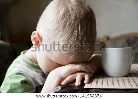 Sad upset tired worried little child (boy) lying on his hands close up portrait