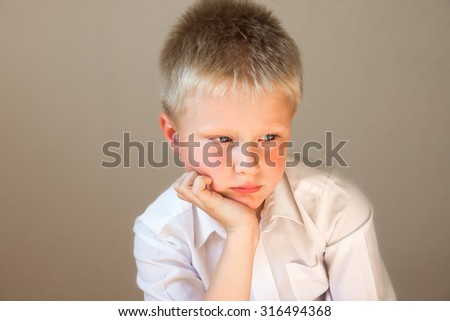 Sad upset tired worried unhappy school child (boy) close up horizontal  portrait with copy space - stock photo