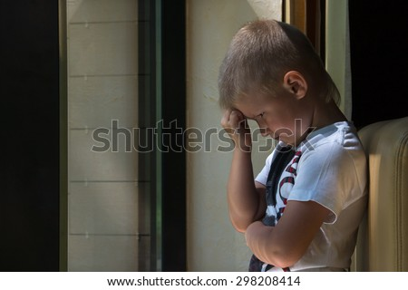 Sad upset waiting boring depressed child (boy) near a window - stock photo