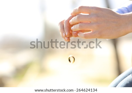 Sad wife hands dropping her wedding ring marriage problems concept - stock photo