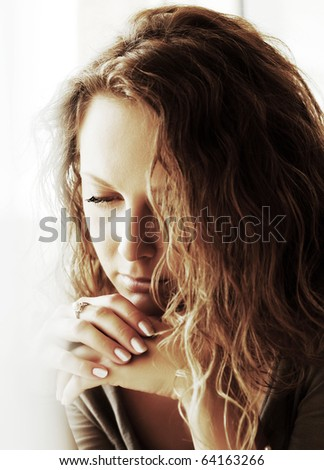 Sad woman against a window. - stock photo