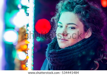 Sad woman by the christmas tree contemplating. Lonely Christmas woman on the winter street at night. Festive brunette feeling sad at christmas looking up