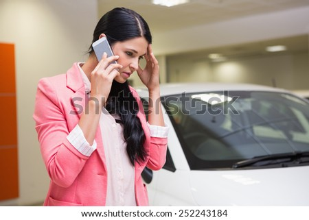 Sad woman calling someone with her mobile phone at new car showroom - stock photo