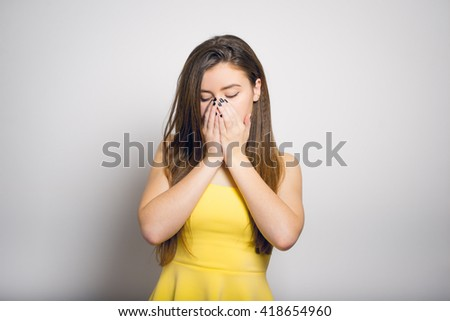 Sad woman covering her face with her hands. On a gray background. - stock photo