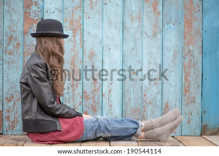 Sad woman deep in thought sitting over grunge wooden background. copy space - stock photo