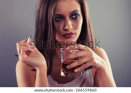Sad woman drinking alcohol and smoking a cigarette - stock photo