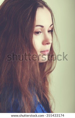 sad woman face close up she is depressed and looking down - stock photo