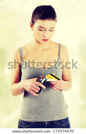Sad woman has to destroy her credit card  - stock photo