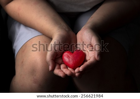 sad woman holding red heart in hand sitting in dark atmosphere present some person need help protection.