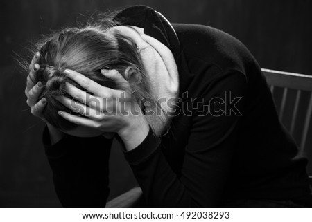 Sad woman holding the head in the hands , black and white