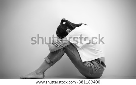 sad woman hug her knee and cry in monochrome - stock photo