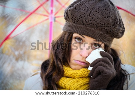 Sad woman in autumn cold rainy day wiping away a tear with a tissue. Depressed female crying and holding umbrella under the rain. - stock photo