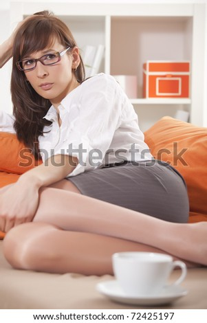 sad woman in business suit on sofa at home