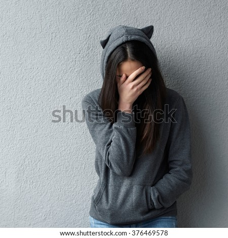 Sad woman in grey hoodie with cat's ears covering face with hand. Wall background. - stock photo