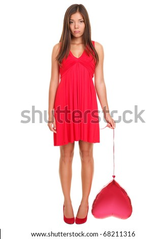 Sad woman in love - funny. Valentines day woman unhappy holding red heart balloon.  Beautiful young woman in red dress. Female model isolated standing on white background. Broken heart love concept.