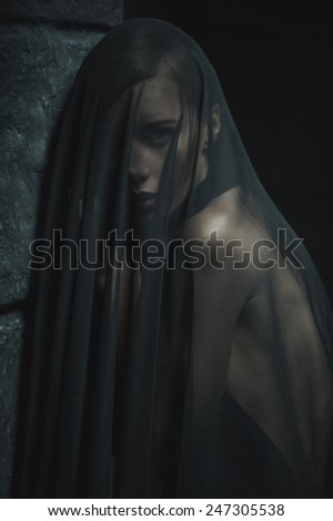 sad woman in mourning black veil  on black wall  background, monochrome image - stock photo
