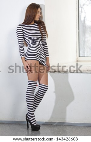 Sad woman in sexy striped shirt and legwarmers standing at the old window - stock photo