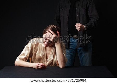 Sad woman is sitting , keeping hand on the forehead, man's figure behind threaten her