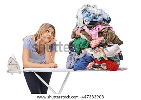 Sad woman leaning on an ironing board and looking at a pile of clothes isolated on white background - stock photo
