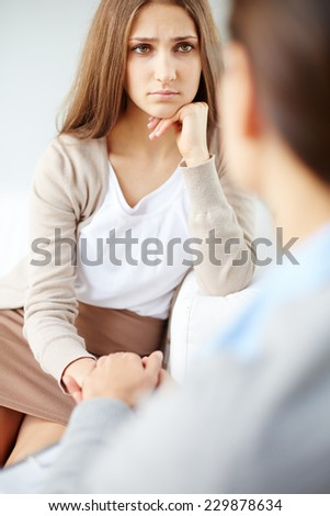 Sad woman looking at psychiatrist while discussing her problem - stock photo